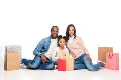 gelukkige Afrikaanse Amerikaanse familie die met het winkelen zakken bij camera glimlachen stock afbeeldingen