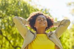Gelukkige Afrikaanse Amerikaanse jonge vrouw in de zomerpark Royalty-vrije Stock Afbeeldingen