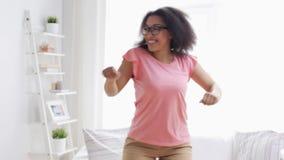 Gelukkige Afrikaanse Amerikaanse jonge vrouw die thuis dansen stock videobeelden