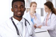 Gelukkige Afrikaanse Amerikaanse mannelijke arts met medisch personeel bij het ziekenhuis Het concept van de geneeskunde stock foto's