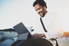 Gelukkige Afrikaanse Amerikaanse mens die e-mail via de elektronische proholding van het aanrakingsstootkussen in handen verzende Stock Foto