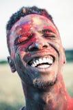 Gelukkige Afrikaanse Amerikaanse mens die met kleurrijke verf van gezicht met gesloten ogen bij holifestival lachen stock fotografie
