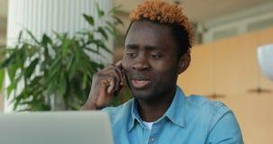 Gelukkige Afrikaanse Amerikaanse mens die telefonisch spreken terwijl het gebruiken van laptop computer in koffie stock footage