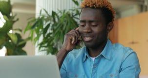 Gelukkige Afrikaanse Amerikaanse mens die telefonisch spreken terwijl het gebruiken van laptop computer in koffie stock videobeelden