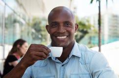 Gelukkige Afrikaanse Amerikaanse mens die van een kop van koffie genieten royalty-vrije stock foto