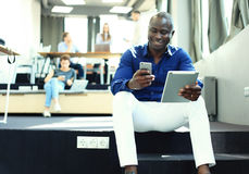 Gelukkige Afrikaanse Amerikaanse ondernemer die tabletcomputer met behulp van royalty-vrije stock foto's