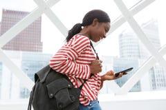 Gelukkige Afrikaanse Amerikaanse vrouw die en cellphonesms-bericht lopen bekijken royalty-vrije stock foto's