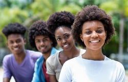 Gelukkige Afrikaanse Amerikaanse vrouw met groep jonge volwassenen in lijn stock foto