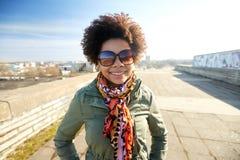 Gelukkige Afrikaanse Amerikaanse vrouw in schaduwen op straat Royalty-vrije Stock Fotografie