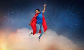 Gelukkige Afrikaanse Amerikaanse vrouw in superhero rode kaap royalty-vrije stock afbeelding
