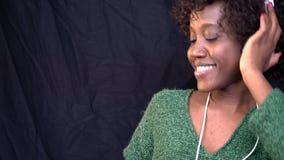 Gelukkige Afrikaanse Amerikaanse vrouw in witte hoofdtelefoons die in de studio dansen en aan muziek, beetje langzame motie luist stock videobeelden