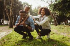Gelukkige Afrikaanse familie die bij het park genieten van stock foto