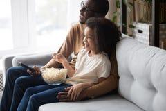 Gelukkige Afrikaanse familiepapa met kinddochter die op TV samen letten royalty-vrije stock afbeelding