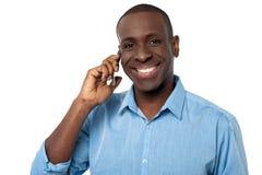 Gelukkige Afrikaanse kerel die een telefoongesprek bijwonen Royalty-vrije Stock Afbeeldingen