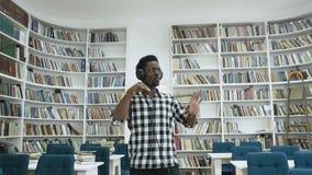 Gelukkige Afrikaanse kerel het luisteren muziek in de hoofdtelefoon en het dansen in de moderne bibliotheek stock video