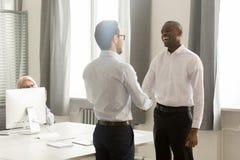 Gelukkige Afrikaanse mannelijke werknemer worden die die gewaardeerd bevorderd door werkgever wordt beloond royalty-vrije stock foto's