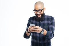 Gelukkige Afrikaanse mens met baard die en mobiele telefoon glimlachen met behulp van Royalty-vrije Stock Foto's