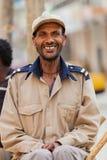 Gelukkige Afrikaanse mensenzitting bij straat het corning glimlachen recht int. Royalty-vrije Stock Foto's