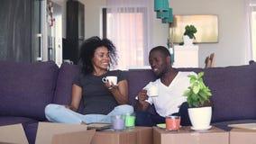 Gelukkige Afrikaanse paar het drinken koffie uitpakkende dozen in nieuw huis stock video