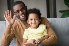 Gelukkige Afrikaanse vader en jong geitjezoons golvende handen die vlog registreren royalty-vrije stock afbeelding