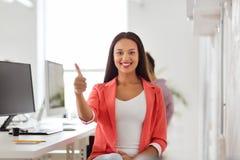 Gelukkige Afrikaanse vrouw die duimen tonen op kantoor Stock Afbeeldingen