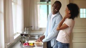 Gelukkige Afrikaanse vrouw die echtgenoot omhelzen die gezonde maaltijd op diner voorbereiden stock footage
