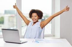 Gelukkige Afrikaanse vrouw met laptop op kantoor stock afbeelding