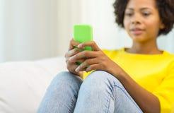 Gelukkige Afrikaanse vrouw met smartphone thuis stock afbeeldingen