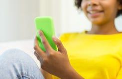 Gelukkige Afrikaanse vrouw met smartphone thuis royalty-vrije stock afbeelding
