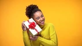 Gelukkige Afrikaanse vrouwelijke holdings huidige doos met rode boog, de verrassing van de verjaardagsgift royalty-vrije stock fotografie