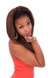 Gelukkige Afro-Amerikaanse jonge vrouw die op wit wordt geïsoleerdo die een kus blazen Royalty-vrije Stock Afbeeldingen