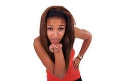Gelukkige Afro-Amerikaanse jonge vrouw die op wit wordt geïsoleerdl die een kus blazen Stock Foto's