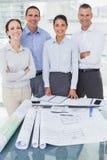Gelukkige architecten die terwijl het samenwerken stellen Stock Afbeeldingen
