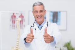 Gelukkige arts die camera met omhoog duimen bekijken Stock Afbeeldingen
