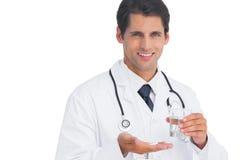 Gelukkige arts die en tabletten en water glimlachen houden Stock Fotografie