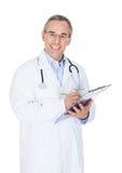 Gelukkige arts die op klembord schrijft Stock Foto