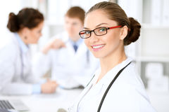 Gelukkige artsenvrouw met medisch personeel bij de het ziekenhuiszitting bij de lijst Rode kaderglazen royalty-vrije stock afbeeldingen
