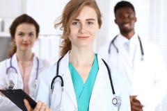 Gelukkige artsenvrouw met medisch personeel bij het ziekenhuis stock afbeelding
