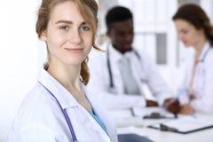 Gelukkige artsenvrouw met medisch personeel bij het ziekenhuis Multi etnische mensengroep stock foto's