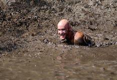 Gelukkige atleet die in de modder zwemmen Royalty-vrije Stock Foto's