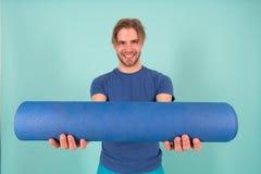 Gelukkige atletenglimlach met yogamat Maniersportman in blauwe t-shirt en borrels Mens met modieus varkenshaar en haar Gymnastiek stock afbeelding