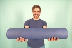 Gelukkige atletenglimlach met yogamat Maniersportman in blauwe t-shirt en borrels Mens met modieus varkenshaar en haar Gymnastiek royalty-vrije stock fotografie