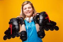 Gelukkige atletische blondevrouw met rolschaatsen op schouder in studio royalty-vrije stock fotografie
