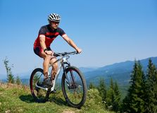 Gelukkige atletische toeristenfietser in helm, zonnebril en volledige materiaal berijdende fiets op grasrijke heuvel stock afbeeldingen