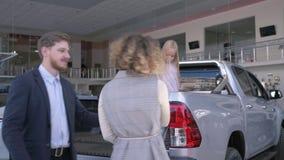 Gelukkige autoaankoop, vrolijke jonge familie met kindmeisje het grappige dansen met sleutels terwijl het kopen van auto in auto stock footage