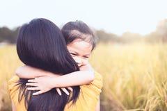 Gelukkige Aziaat weinig kindmeisje die haar moeder met liefde koesteren stock fotografie