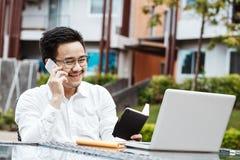 Gelukkige Aziatische Bedrijfsmens die met partner aan telefoon werken Jong Ha Stock Fotografie