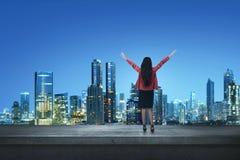 Gelukkige Aziatische bedrijfsvrouw die zich op een rand een dak bevinden stock fotografie