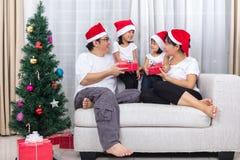 Gelukkige Aziatische Chinese Kerstmisgift van de familieuitwisseling thuis stock afbeeldingen