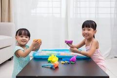 Gelukkige Aziatische Chinese meisjes die kinetisch zand thuis spelen Stock Foto